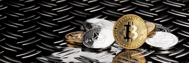 stack of crypto currency coins stack on shiny metal diamond plate dark black financial business panorama background bitcoin ethereum litecoin monero dash iota ripple