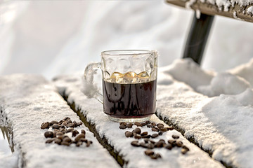 Mug of black espresso coffee stands in the snow, a wooden bench in the park, winter, scattered beans