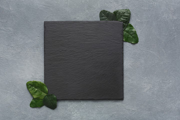 Empty square black slate plate on grey background