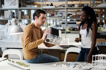 Multiracial couple working in design and engineering architecture office.