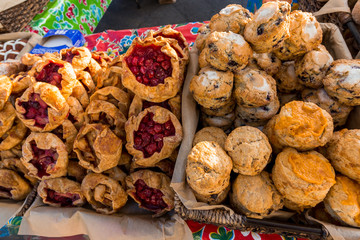 Several different pastries for sale at a farmers market.