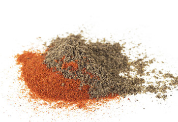 Pile of red and black pepper powder on a white background