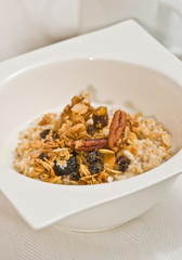 Close up, top view of a square, deep, white bowl of granola with raisins and walnut halves with skim milk on a white place mat, paleo diet