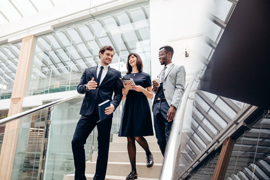 Three happy multiracial business people walking down on stairs together with digital tablet