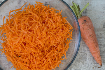 Grated carrots in a glass bowl. A whole carrot to the side.