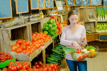 Lady in farm shop holding basket of produce