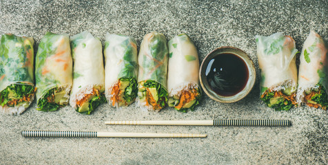 Helathy Asian cuisine. Flat-lay of vegan spring rice paper rolls with vegetables, soy sauce, chopsticks over concrete background, top view, wide composition. Clean eating, vegetarian food