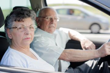 happy senior couple sitting inside their car