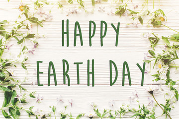 happy earth day text sign on beautiful lilac and daisy flowers on rustic white wooden background top view. greeting card. environmental concept. earth day. save environment. eco