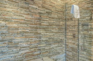 Stone wall in shower with glass surround