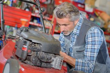 worker repairing lawnmower motor