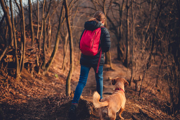 Girl hiking on forest trail with dog