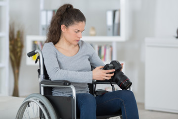 female photographer in a wheelchair holding a professional camera