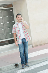 Man on telephone, waiting to cross the road