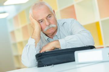 sad senior man sitting at table at the office