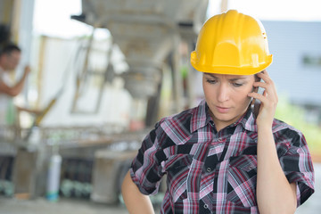young woman wearing a hardhat talking on the phone
