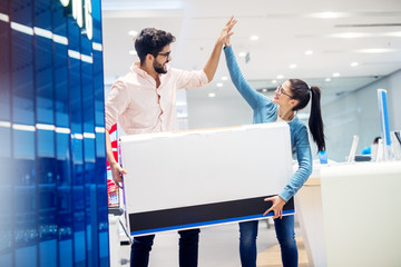 Portrait view of cute satisfied charming happy young student girl clapping hands with her bearded handsome smiling boyfriend while holding box after shopping in a tech store.