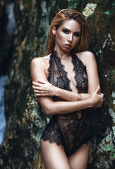 Fashion Vogue style beauty photo shoot of sexy blonde girl model in black lace body or bodysuite. Rock, jungle and waterfall at background. Close up portrait of beautiful young woman