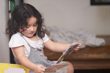 Cute three year old girl enjoy reading a book.