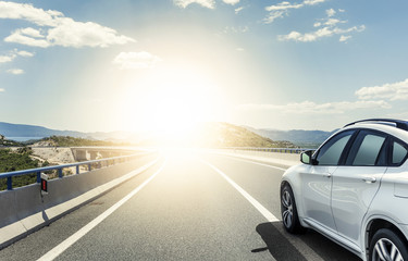A white car rushing along a high-speed highway in the sun. Wall mural