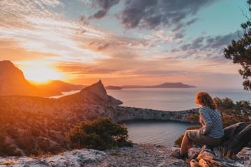 A tourist girl admires the picturesque sunrise