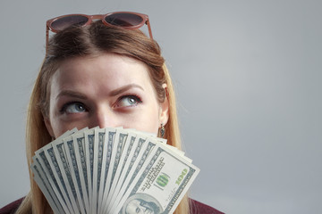 A girl in a burgundy sweatshirt covers her face with hundred-dollar bills.