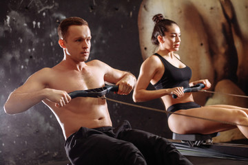 Athletic couple training on row machine at cross gym
