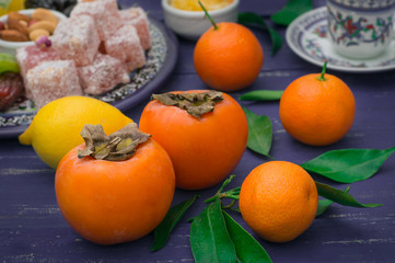 Set of fruits. Tangerines, persimmons, lemon with oriental sweets, rahat lokum. Selective focus. Wooden blue rustic background. Top view