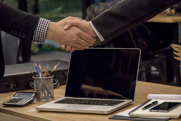 Business man shaking hands for good deals over office table at meeting room.