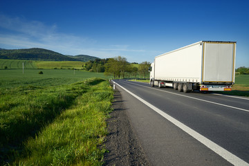 Fotobehang - White truck on the asphalt road between green fields in rural landscape with wooded mountains in background