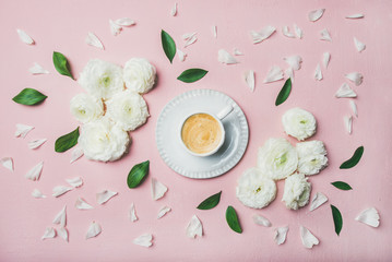Spring morning concept. Flat-lay of cup of coffee surrounded with white ranunculus flowers and petals over light pink pastel background, top view