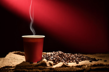 Paper cup of coffee with smoke and coffee beans on reddish brown background