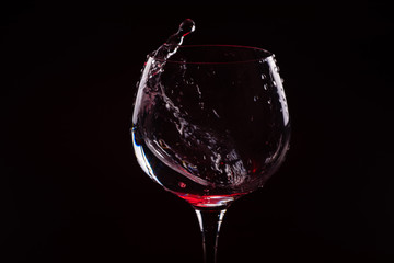 Red wine splashing out of a tall wine glass