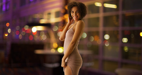 Sexy black woman modeling with bokeh lights in casino