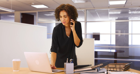 Businesswoman using laptop computer in office while listening on smartphone device