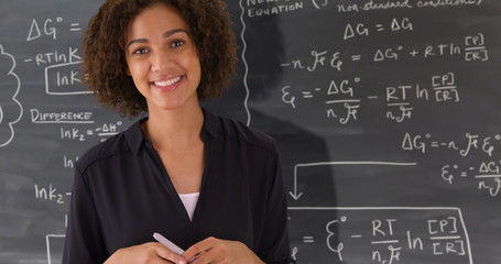 Portrait of black teacher giving math lesson on chalkboard