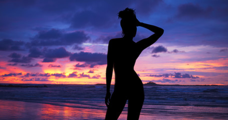Single silhouette of sensual woman standing on sunset beach in Hawaii