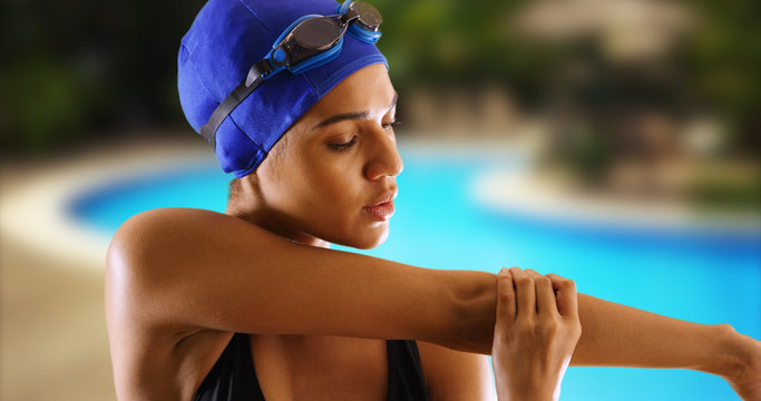 Closeup of African swimmer stretching upper body by pool