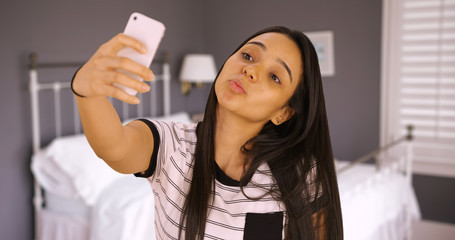 A cute teen takes a selfie in her bedroom with the duck face. A young girl takes a picture of herself with her smart phone