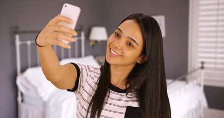 A cute teen takes a selfie in her bedroom. A young girl takes a picture of herself with her smart phone