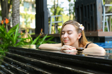 healthy blonde woman enjoy spa outside on sunny day. concept of relaxation, place or resort with a mineral spring swimming pool
