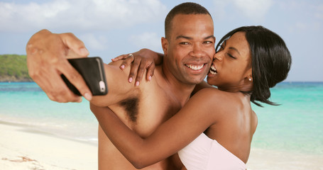 Engaged couple on honeymoon taking selfies on Caribbean beach. Man and woman with smartphone being silly and playful