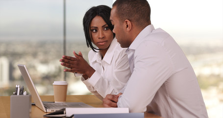 Team of two business people working together in workplace using laptop computer. African American businessman and businesswoman working in office with city view. Man and woman in corporate building.
