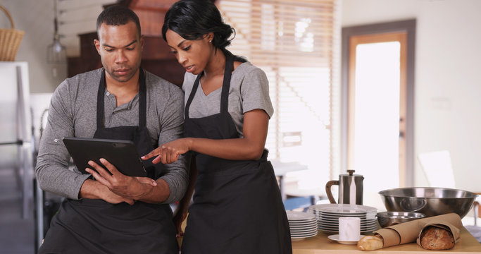 Small business owner showing employee new plan on tablet computer. African American woman running bakery with husband