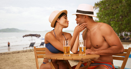 African American couple flirt while drinking at the beach. A black man and woman get drunk on the Costa Rican shore