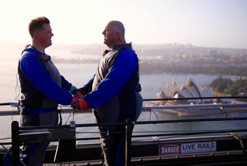 Warren Orlandi and Pauly Phillips react after they became the first same-sex couple to marry atop of the Sydney Harbour Bridge, just two days out from the 40th anniversary of the Sydney Gay and Lesbian Mardi Gras