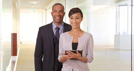 African American man and woman posing for a portrait in their office building. Black business couple holding a tablet in a corporate hallway