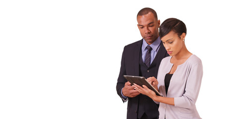 African American couple working in corporate business working on their tablet. Two black business professionals working on their pad on a white background