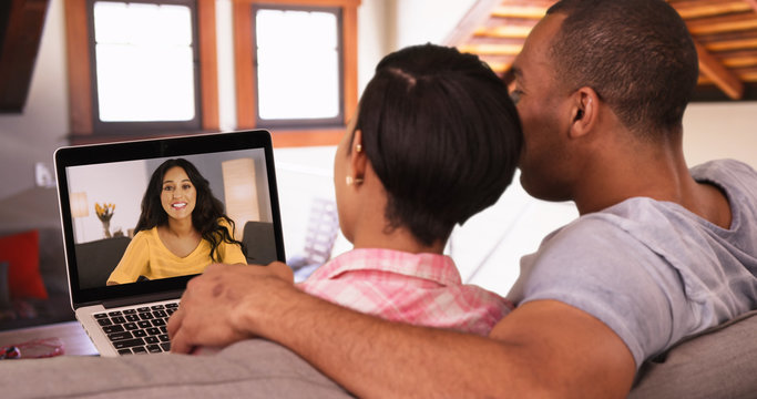 A black couple has a video call with their Caucasian friend. An African American man and woman video chat with a white girl
