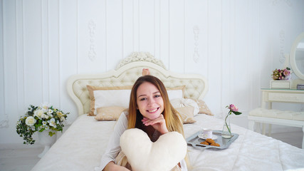 Young Smiling Woman Closes Face Beige Pillow-Hearted, Laughing and Smiling at Beautiful Beige Double Bed With Pillows in White Room, Large Bedroom. Well-Groomed Woman Removed For Cosmetic and